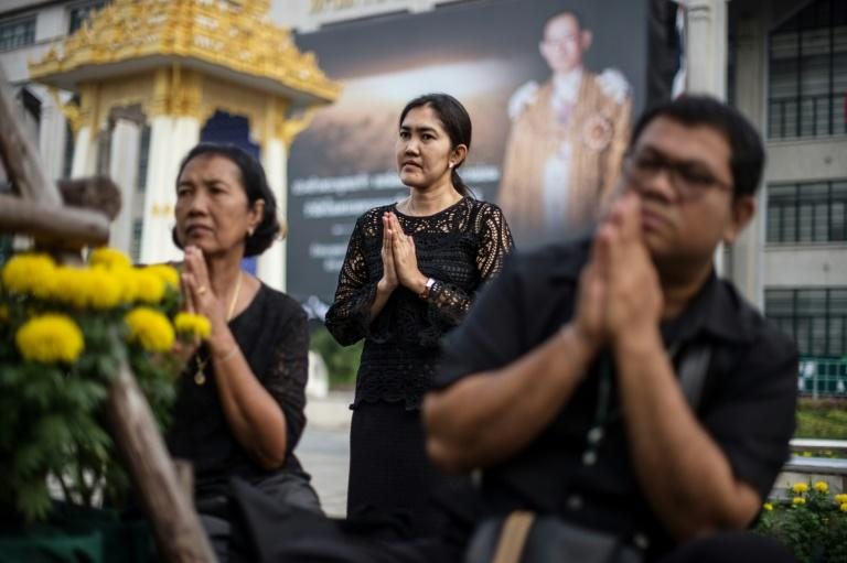Thai civil servants pray during a ceremony led by monks in front of Bangkok's City Hall marking one year since the death of King Bhumibol Adulyadej