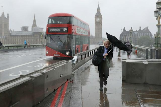 <p>A man with an umbrella in the wind walks by newly installed barriers on Westminster Bridge in London on Tuesday, June 6, 2017. (Photo: Matt Dunham/AP) </p>