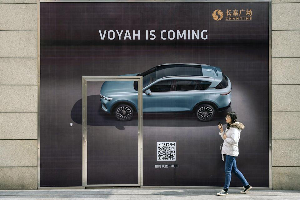 A shopper walks past Dongfeng Motor's yet-to-open Voyah showroom at the Chamtime Plaza in Shanghai on Monday, March 8, 2021. Photo: Bloomberg