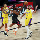 Houston Rockets guard James Harden, center, passes the ball while defended by Los Angeles Lakers forward Kyle Kuzma, left, and forward Anthony Davis, right, during the first half of an NBA basketball game Thursday, Aug. 6, 2020, in Lake Buena Vista, Fla. (Kim Klement/Pool Photo via AP)