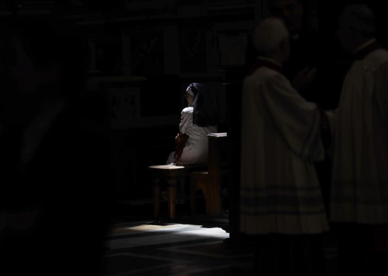 FILE - In this Tuesday, June 26, 2018 file photo, a ray of sun sheds light on nun sitting inside the Basilica of St. John Lateran in Rome. The Vatican is facing a dilemma after nearly all the nuns in a tiny French religious order threatened to renounce their vows rather than accept the removal of their superior. The standoff marks an extraordinary battle of wills between the Vatican and the group of 39 nuns who run homes for the aged in rural France. (AP Photo/Alessandra Tarantino, File )