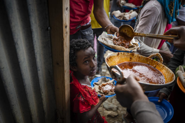 Elena, 7, center, lines up with other displaced Tigrayans to receive food donated by local residents at a reception center for the internally displaced in Mekele, in the Tigray region of northern Ethiopia, on Sunday, May 9, 2021. The 15 kilograms of wheat, half a kilogram of peas and some cooking oil per person, to last a month — was earmarked only for the most vulnerable. That included pregnant mothers and elderly people. (AP Photo/Ben Curtis)