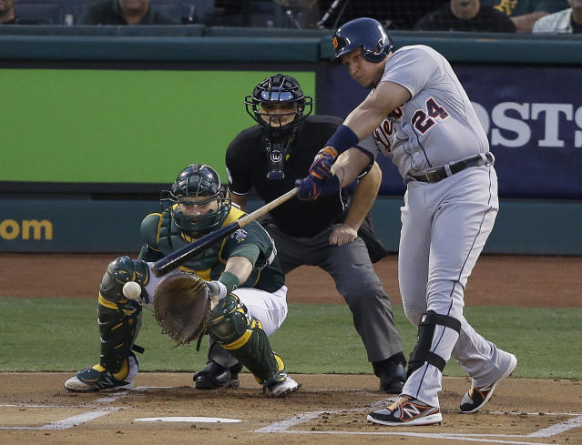 Detroit Tigers' Miguel Cabrera (24) hits a single to score Austin Jackson during the first inning of Game 1 of the American League baseball division series against the Oakland Athletics in Oakland, Calif., Friday, Oct. 4, 2013. At rear are Athletics catcher Stephen Vogt and umpire Mark Wegner. (AP Photo/Jeff Chiu)