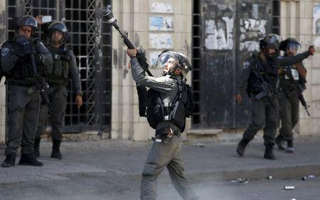 An Israeli border police fires at Palestinian protesters during clashes following a protest against the Israeli police raid on Jerusalem's al-Aqsa mosque on Tuesday, in the occupied West Bank city of Hebron September 18, 2015. REUTERS/Mussa Qawasma