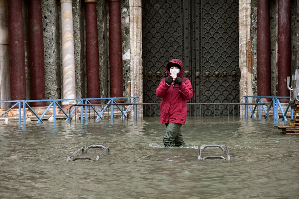 "A person takes photos while standing on a flooded St. Mark's Square on December 8, 2020 in Venice following a high tide ""Alta Acqua"" event following heavy rains and strong winds, and the mobile gates of the MOSE Experimental Electromechanical Module that protects the city of Venice from floods, were not lifted (Photo by ANDREA PATTARO / AFP) (Photo by ANDREA PATTARO/AFP via Getty Images)"
