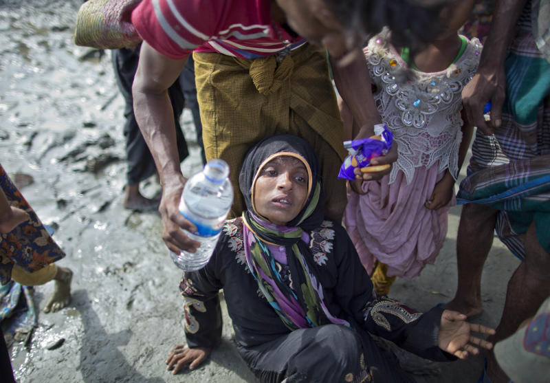 A Rohingya Muslim Mohamed Rafiq hands a drink of water and biscuits to his wife Noora Khatum who lies exhausted on the ground as they reach Teknaf, Bangladesh, Friday, Sept. 29, 2017. He trekked to Bangladesh as part of an exodus of a half million people from Myanmar, the largest refugee crisis to hit Asia in decades. But after climbing out of a boat on a creek on Friday, Rafiq could go no further. He collapsed onto a muddy spit of land cradling his wife in his lap, a limp figure so exhausted and so hungry she could no longer walk or even raise her wrists. (AP Photo/Gemunu Amarasinghe)