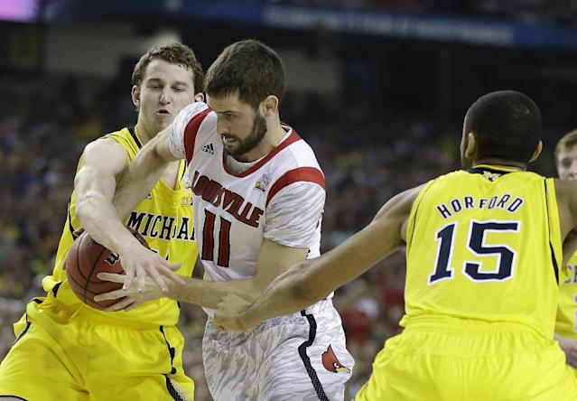 Louisville guard/forward Luke Hancock (11) drives past Michigan guard Nik Stauskas (11) during the first half of the NCAA Final Four tournament college basketball championship game Monday, April 8, 2013, in Atlanta. (AP Photo/Charlie Neibergall)
