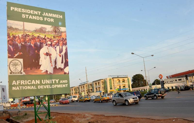 Cars drive by a poster for Gambian President Yahya Jammeh on November 22, 2011 in Banjul