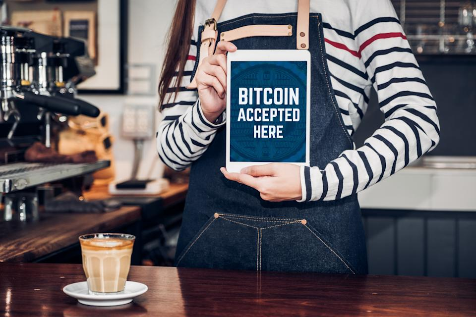 Close up woman barista holding tablet and show bitcoin accepted here on tablet screen at cafe counter.