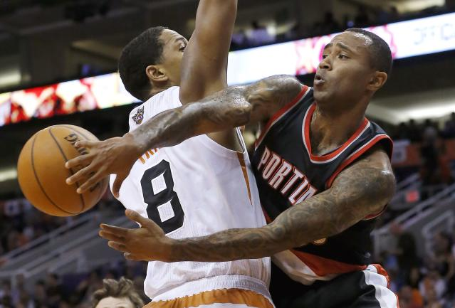 Portland Trail Blazers' Mo Williams passes the ball around Phoenix Suns' Channing Frye (8) during the first half in an NBA basketball game Wednesday, Oct. 30, 2013, in Phoenix. (AP Photo/Ross D. Franklin)