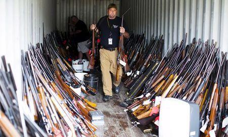 Chesterfield County Sheriff's lieutenant David Lee removes rifles from a shipping container as he and other officers sort through thousands of guns found in the home and garage of Brent Nicholson, in Pageland, South Carolina, November 10, 2015. REUTERS/Jason Miczek