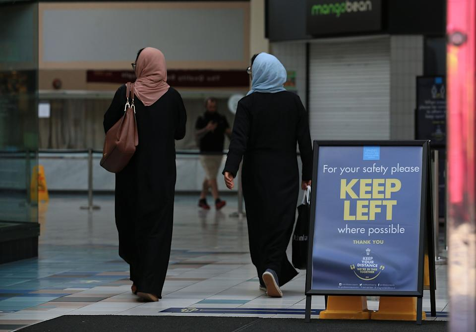 Women walk in a socially distanced one-way system, implemented due to COVID-19, inside a shopping centre in Oldham, Greater Manchester, northwest England on August 20, 2020. - Oldham, as of Thursday, has one of the highest rates of new COVID-19 infections, and could be subject to a imposed Local Lockdown to prevent the spread of the novel coronavirus. (Photo by Lindsey Parnaby / AFP) (Photo by LINDSEY PARNABY/AFP via Getty Images)