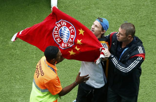 Stewards escort a Germany fan waving a Bayern Munich towel off the pitch during the team's 2014 World Cup Group G soccer match against the U.S. at the Pernambuco arena in Recife June 26, 2014.REUTERS/Ruben Sprich (BRAZIL - Tags: SOCCER SPORT WORLD CUP)