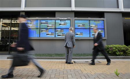 A man looks at an electronic board displaying Japan's Nikkei average (top C) and various countries' stock indices, as passers-by walk past outside a brokerage in Tokyo April 16, 2014. REUTERS/Toru Hanai