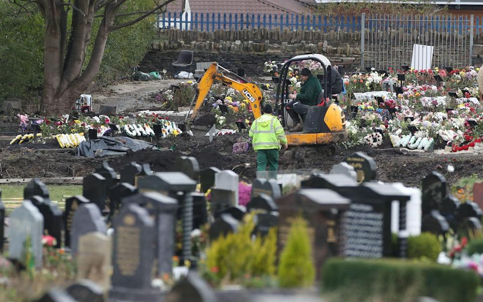 Workers use machinery to dig graves in Bradford, West Yorkshire, where it was reported that services struggled to keep up with the number of burials due to coronavirus - Danny Lawson/PA