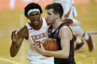 Oklahoma guard Austin Reaves, right, is defended by Texas forward Kai Jones (22) during the second half of an NCAA college basketball game Tuesday, Jan. 26, 2021, in Austin, Texas. (AP Photo/Eric Gay)