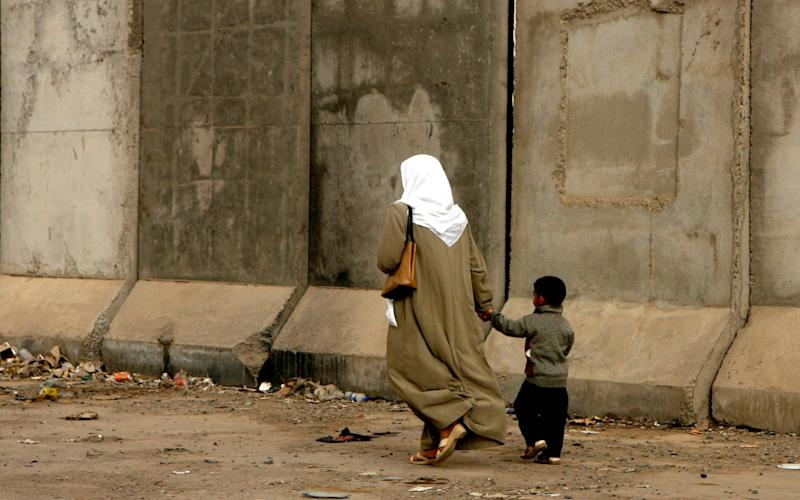 An Iraqi woman and child walking past concrete security walls in Baghdad in 2008 - Credit: Heathcliff O'Malley/-
