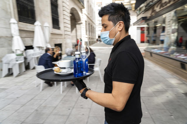 A waiter with his mask takes a service to a terrace in Santander, Spain, on May 12, 2020, which with the arrival of phase 1 of de-escalation, can already open although the number of tables and diners is limited. (Photo by Joaquin Gomez Sastre/NurPhoto via Getty Images)