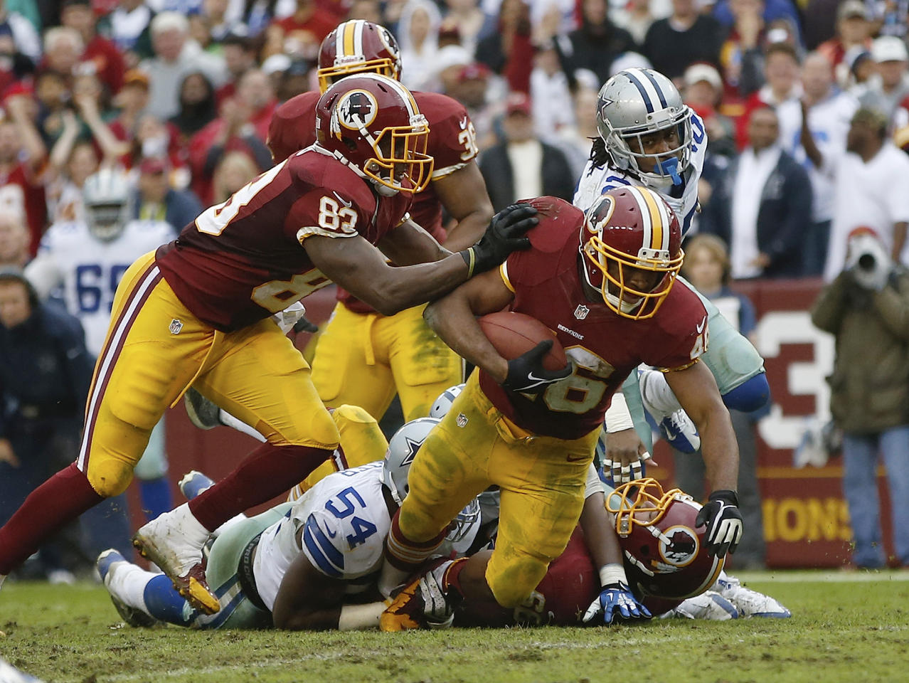 Washington Redskins running back Alfred Morris is dragged down by Dallas Cowboys outside linebacker Bruce Carter (54) during the second half of an NFL football game in Landover, Md., Sunday, Dec. 22, 2013. (AP Photo/Evan Vucci)