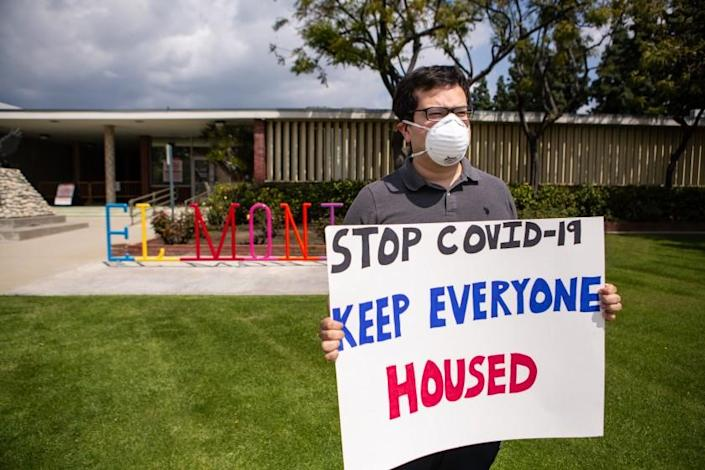 EL MONTE, CA - MARCH 29: Rodolfo Cortes, 30, of El Monte and other tenant rights activists assemble at the El Monte City Hall to demand that the El Monte City Council pass an eviction moratorium barring all evictions during the coronavirus pandemic on Sunday, March 29, 2020 in El Monte, CA. (Jason Armond / Los Angeles Times)