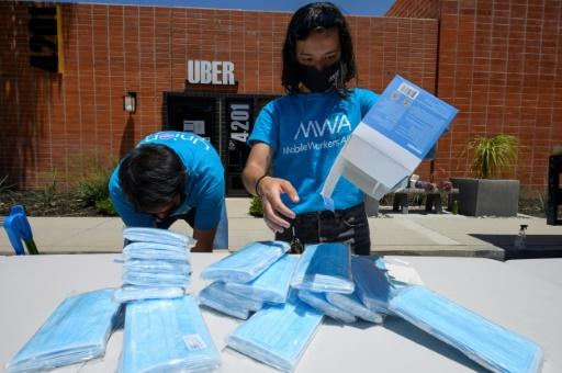 Workers prepare face masks for rideshare drivers impacted by the COVID-19 pandemic at a food drive organised by the Mobile Workers Alliance (MWA), outside the Uber Greenlight hub in Burbank, California, June 11, 2020