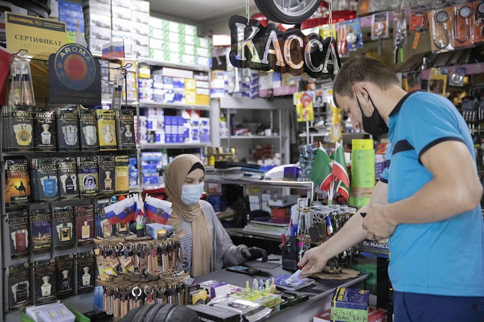 A cashier tends to a customer in an automotive parts store amid the ongoing COVID-19 pandemic; the coronavirus lockdown still in effect with the curfew from 8 p.m. to 8 a.m. and borders closed, car repair shops, small stores and service businesses have started reopening in Chechnya. (Photo by Yelena Afonina\TASS via Getty Images)