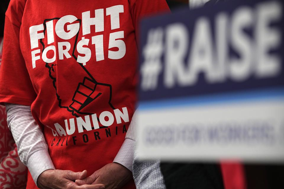 "WASHINGTON, DC - JULY 18:  An activist wears a ""Fight For $15"" T-shirt during a news conference prior to a vote on the Raise the Wage Act July 18, 2019 at the U.S. Capitol in Washington, DC. The legislation would raise the federal minimum wage from $7.25 to $15 by 2025.  (Photo by Alex Wong/Getty Images)"