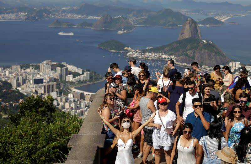 A tourist wearing a protective face mask poses for a photo during a visit to the statue of Christ the Redeemer after reports of coronavirus in Rio de Janeiro