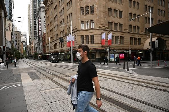 A Sydney man wears a mask on a near-deserted street in the central business district as people stay home due to the COVID-19 novel coronavirus outbreak.