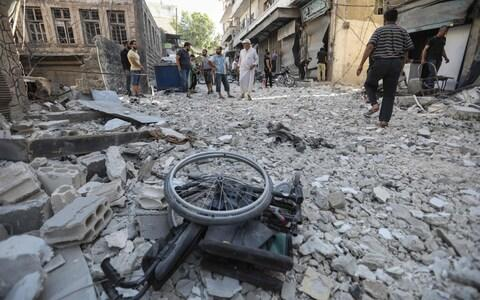 A wheelchair is seen amid the rubble of destroyed buildings following a reported regime air strike on the town of Ariha - Credit: OMAR HAJ KADOUR/AFP/Getty Images
