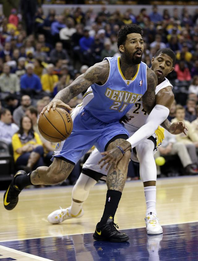 Indiana Pacers forward Paul George, right, reaches around Denver Nuggets forward Wilson Chandler (21) as he drives the baseline in the first half of an NBA basketball game in Indianapolis, Monday, Feb. 10, 2014. (AP Photo/Michael Conroy)