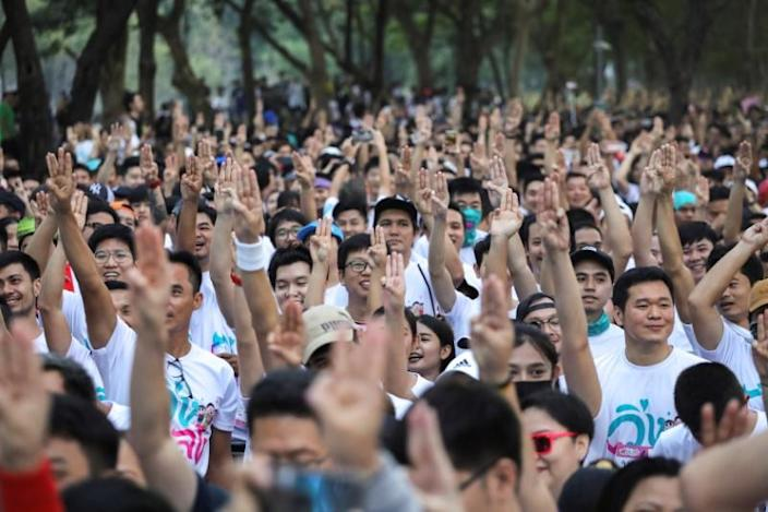 """Runners flash three finger salute as they attend at """"Run Against Dictatorship"""" event at a Public park in Bangkok"""