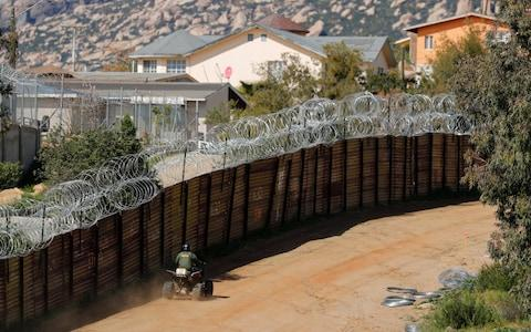 A US Customs and Border Patrol agent travels along the border wall between the US and Mexico near Tecate, California - Credit:  MIKE BLAKE/Reuters