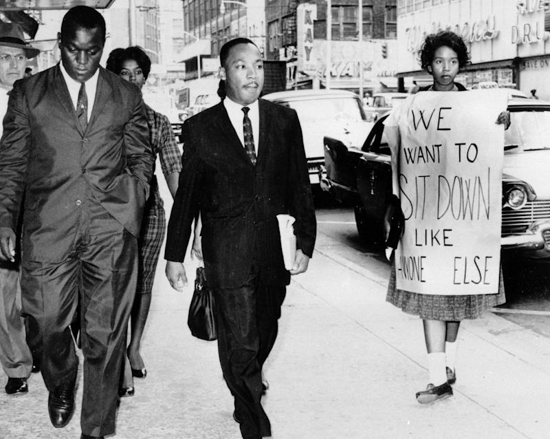 Dr. Martin Luther King Jr. under arrest by Atlanta Police Captain R.E. Little, left rear, passes through a picket line in front of a downtown department store on Oct. 9, 1960. With King is another demonstration leader, Lonnie King and an unidentified woman. Dr. Martin Luther King Jr. was among the 48 African-Americans arrested following demonstrations at several department and variety stores protesting lunch counter segregation.