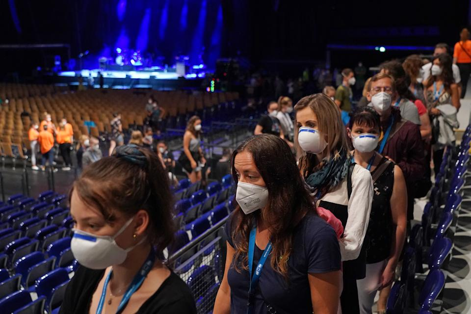 LEIPZIG, GERMANY - AUGUST 22: Participants wearing FFP2 protective face masks take part in the RESTART-19 Covid transmission risk assessment study in a concert setting during a break for concessions at an indoor arena during the coronavirus pandemic on August 22, 2020 in Leipzig, Germany. The study, organized by the University Hospital of Halle (Saale), simulates a live concert venue with several thousand audience members in three different scenarios in order to develop risk reduction measures for large events. Participants wear tracer devices to track their movements and sensors measure aerosol currents in the arena. All participants had to undergo a Covid-19 test within the last 48 hours and test negative in order to take part.  (Photo by Sean Gallup/Getty Images)