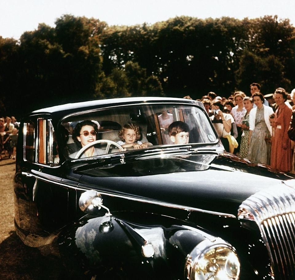 <p>In one of her first driving photos, the Queen chauffeured her two young children, Prince Charles and Princess Anne, as onlookers gathered around them. </p>
