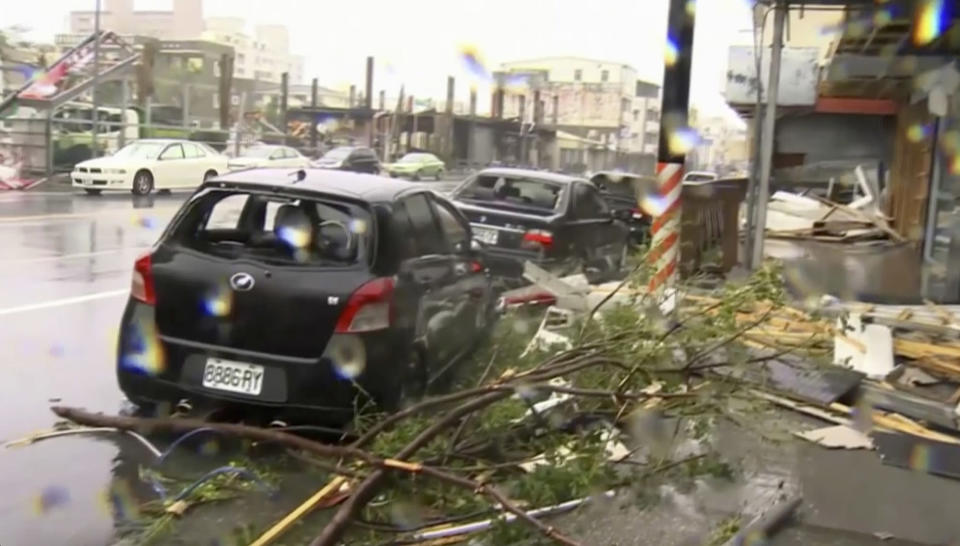 <p>In this image made from video, wind-blown debris from Typhoon Nepartak litters the street and damages a vehicle in Taitung, south eastern Taiwan, Friday, July 8, 2016. (EBC via AP Video) </p>
