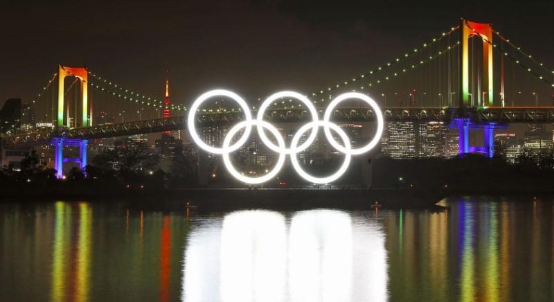 Fireworks light up the sky near the illuminated Olympic rings at a ceremony to mark six months before the start of the 2020 Olympic Games in Tokyo
