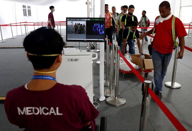 FILE PHOTO: Contractors and workers pass a thermal scanner as part of the coronavirus outbreak precautions during a media preview of the Singapore Airshow in Singapore