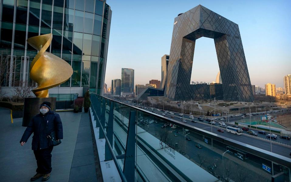 A man walks along an observation deck near the Beijing headquarters of CCTV, the state-owned broadcaster that owns CGTN, earlier in February - Mark Schiefelbein/AP