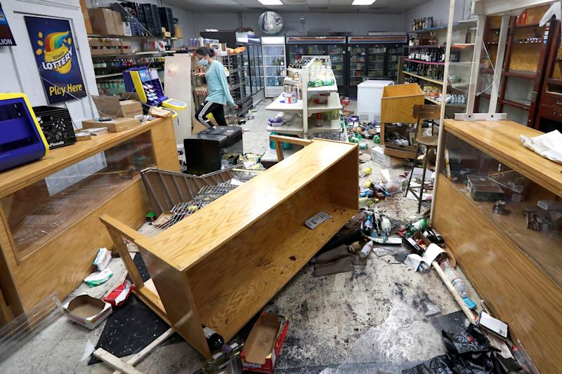 Kajal Dalal walks through her family's food and liquor store in downtown Chicago on Monday after it was vandalized. (Photo: AP Photo/Charles Rex Arbogast)