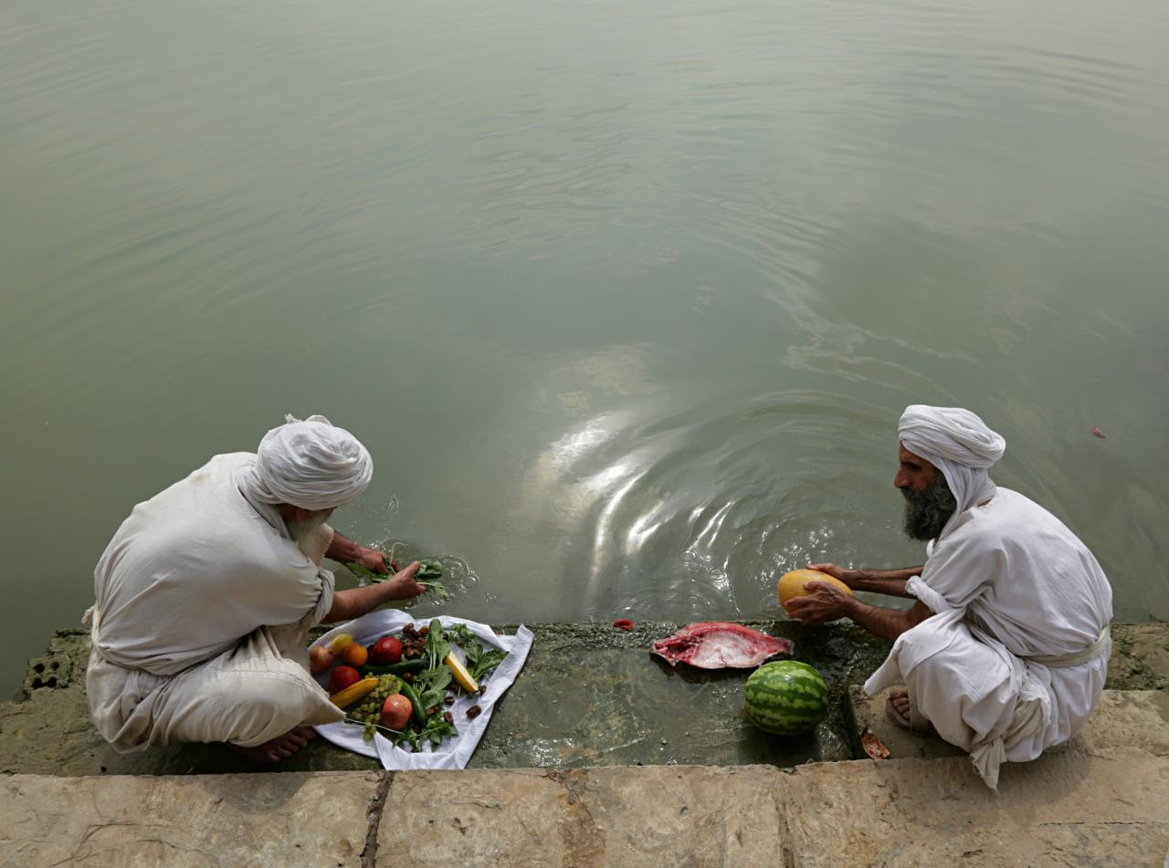 In this Sunday, Oct. 14, 2018 photo, followers of the obscure and ancient Mandaean faith wash food with river water along a strip of embankment on the Tigris River reserved for them, in Baghdad, Iraq. Every Sunday worshippers bathe themselves in the waters to purify their souls. But unlike in ancient times, the storied river that runs through Baghdad is fouled by the smells of untreated sewage and dead carp, which float by in the fast-moving current. (AP Photo/Hadi Mizban)