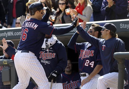 Minnesota Twins' Josh Willingham, left, is welcomed at the dugout after hitting a 2-run home run off Detroit Tigers pitcher Rick Porcello in the third inning of a baseball game, Thursday, April 4, 2013, in Minneapolis. (AP Photo/Jim Mone)