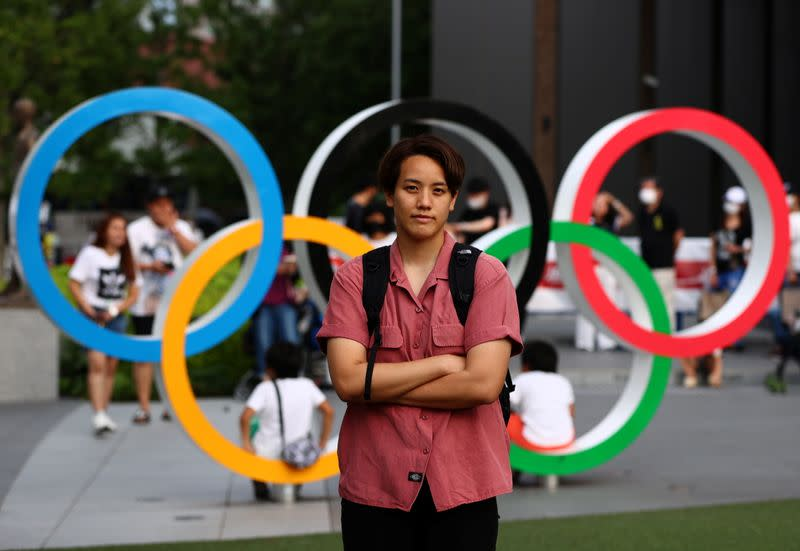 Tsubata, nurse and boxer, poses in front of the Olympic Rings in Tokyo