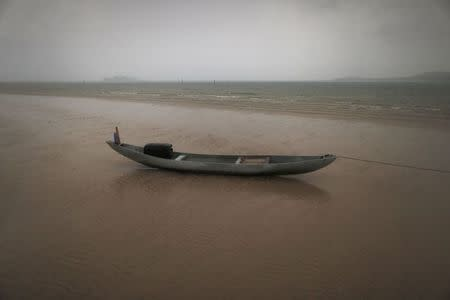 Fishing boat sits on a beach during a rain storm on the east coast of Natuna Besar