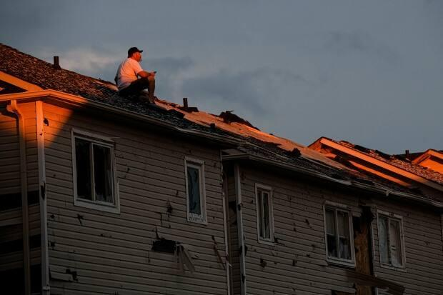 A man surveys the damage left after a tornado touched down in his neighbourhood in Barrie, Ont., on Thursday. (Christopher Katsarov/Canadian Press - image credit)