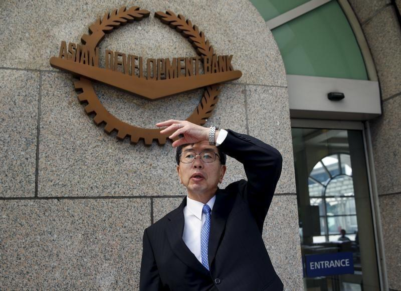 ADB President Nakao gestures at the entrance of ADB headquarters in Mandaluyong, Metro Manila