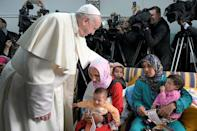 Pope Francis touches child's head during a visit to a rural social service run by the Daughters of Charity of St. Vincent de Paul in Temara, near Rabat, Morocco March 31, 2019. Vatican Media/Handout via REUTERS