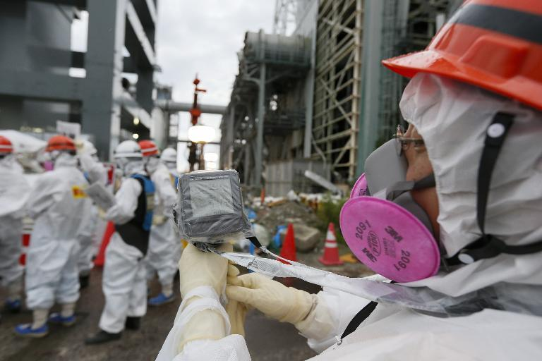 A TEPCO employee measures radiation levels as workers construct an ice wall at the tsunami-crippled Fukushima nuclear power plant in Okuma, Fukushima Prefecture, on July 9, 2014