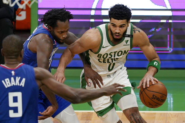 Boston Celtics forward Jayson Tatum (0) drives against Los Angeles Clippers guard Patrick Beverley, left, and center Serge Ibaka (9) in the third quarter of an NBA basketball game, Tuesday, March 2, 2021, in Boston. (AP Photo/Elise Amendola)